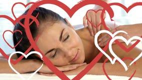 Masajista que hace masaje a las mujeres atractivas relajadas en el balneario con los corazones para día de San Valentín metrajes