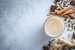 Masala chai with spices. Masala chai in glass cup with ingredients spices cinnamon, cardamom, ginger on a light blue stone background. Top view, horizontal image Royalty Free Stock Photography