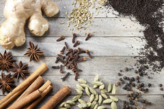 Masala Chai Tea Ingredients. Chai tea ingredients with cinnamon, cloves, fennel seeds, cardamon, ginger, star anise, black pepper and black tea on a rustic wood Royalty Free Stock Image