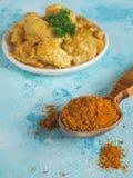 Masala pikantność w drewnianej łyżce i talerzu z kurczakiem polędwicowym w curry'ego kumberlandzie zdjęcia stock