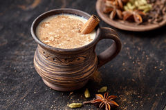 Masala pulled tea chai latte homemade hot Indian sweet milk spiced drink, ginger, fresh spices and herbs blend Stock Photos