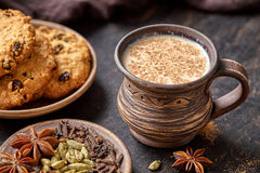 Masala pulled tea chai latte traditional hot Indian sweet milk spiced drink, ginger, fresh spices and herbs blend Stock Images