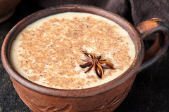 Masala tea chai latte traditional homemade warm Indian sweet milk spiced drink, ginger, fresh spices blend. Organic infusion healthy wellness beverage in rustic Royalty Free Stock Photo
