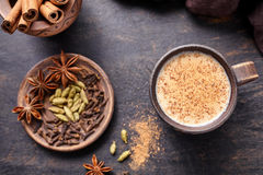 Masala tea chai latte traditional hot Indian sweet milk spiced drink, nutmeg, ginger, cinammon sticks Stock Photo
