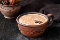 Masala tea chai latte traditional warm Indian sweet milk spiced drink, ginger, herbs. Spices blend organic infusion healthy wellness beverage in rustic clay Stock Image
