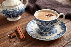 Masala tea chai latte traditional warm Indian sweet milk with spices, cinnamon stick, herbs blend organic infusion. Healthy beverage in porcelain cup on wooden Royalty Free Stock Images