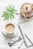 Masala tea, teapot, notepad, glasses, pen, green flower leaf on white background, top view. Morning inspiration planning. Flat lay stock image