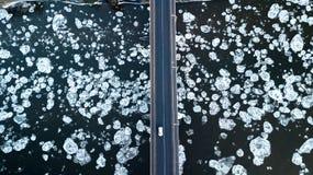 Masas de hielo flotante de hielo que flotan en el río Puente del río Opinión del ojo del ` s del pájaro fotografía de archivo libre de regalías