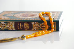 The Masbaha, also known as Tasbih with the Quaran. The Masbaha is also known as Tasbih photographed here with the Quran Arabic Tea and dried dates - all symbols Stock Photos