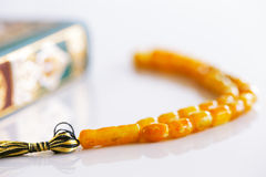 The Masbaha, also known as Tasbih with the Quaran. The Masbaha is also known as Tasbih photographed here with the Quran Arabic Tea and dried dates - all symbols Royalty Free Stock Photography