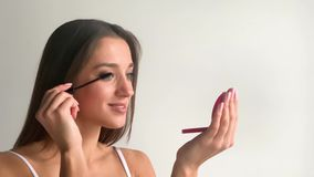 mascara Μακριά κινηματογράφηση σε πρώτο πλάνο μαστιγίων Όμορφη γυναίκα που εφαρμόζει mascara στα μάτια της απόθεμα βίντεο