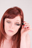 Mascara. A woman putting on her mascara with a brush Royalty Free Stock Photo
