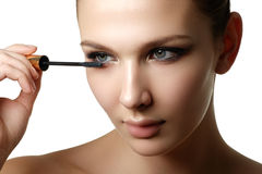 Mascara applying closeup, long lashes. Mascara brush. Eyelashes royalty free stock images