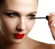Mascara applying closeup, long lashes. Mascara brush. Eyelashes. Extensions. Make-up for blue eyes. Eye make up apply. Young beautiful woman applying mascara Stock Photos