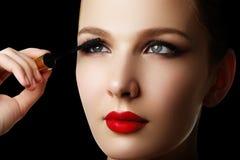 Mascara applying closeup, long lashes. Mascara brush. Eyelashes. Extensions. Make-up for blue eyes. Eye make up apply. Young beautiful woman applying mascara Stock Photography