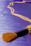 Mascara brush with golden chain over blue silk Stock Image