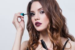 Mascara. Closeup Of Beautiful Young Woman Face With Beauty Makeup, Fresh Soft Skin And Long Black Thick Eyelashes Applying Mascara royalty free stock image