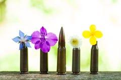 Mascaramento da bala entre flores fotografia de stock