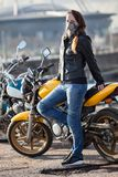 Mascarilla del cuello del motorista de la mujer que lleva joven que presenta detrás de su bici de la calle al aire libre Fotos de archivo libres de regalías