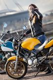 Mascarilla del cuello del motorista de la mujer que lleva joven que se coloca al lado de la bici de la calle al aire libre Fotos de archivo