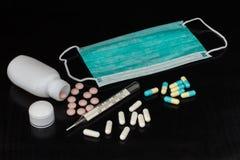 Mascarilla, termómetro de mercurio y diversas píldoras con la botella o fotos de archivo