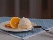 Mascarpone ice-cream scoop served with a slice of orange. stock photo