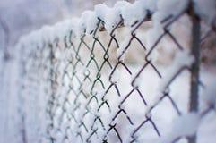 Maschenzaun bedeckt in einer starken Schneeschicht Lizenzfreie Stockfotos