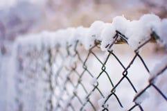 Maschenzaun bedeckt in einer starken Schneeschicht Stockfoto