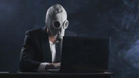 Maschera antigas d'uso dell'uomo d'affari che funziona al computer portatile in ufficio scuro video d archivio