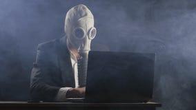 Maschera antigas d'uso dell'uomo d'affari che funziona al computer portatile in ufficio scuro stock footage