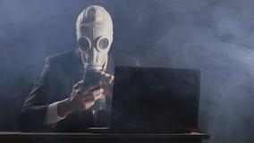 Maschera antigas d'uso dell'uomo d'affari che funziona allo smartphone in ufficio scuro archivi video