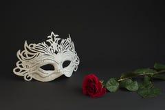 Maschera bianca di carnevale e una rosa su un fondo grigio Immagine Stock
