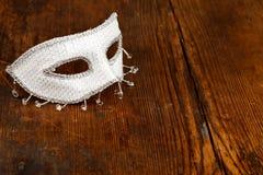 Maschera bianca sulla tavola di legno fotografie stock