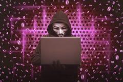 Maschera d'uso dell'uomo incappucciato che scrive sul computer portatile Fotografie Stock