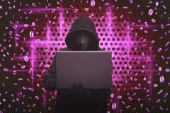 Maschera d'uso dell'uomo incappucciato che scrive sul computer portatile Immagine Stock