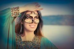 Maschera d'uso della giovane donna e vestito orientale fotografia stock libera da diritti