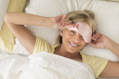 Maschera d'uso di sonno della donna felice sul letto Immagini Stock Libere da Diritti