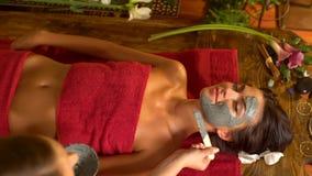 Maschera del corpo dell'argilla e di massaggio nel salone della stazione termale Vista superiore 4K archivi video