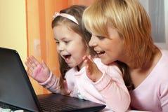 Maschera della madre e del bambino con il computer portatile Immagini Stock Libere da Diritti