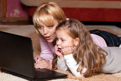Maschera della madre e del bambino con il computer portatile Immagine Stock