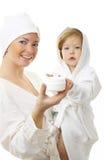 Maschera della madre felice con la crema della holding del bambino immagine stock
