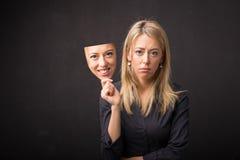 Maschera della tenuta della donna del suo fronte felice Fotografie Stock Libere da Diritti