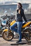 Maschera di protezione d'uso del collo del motociclista della giovane donna che posa dietro la sua bici della via all'aperto fotografie stock libere da diritti