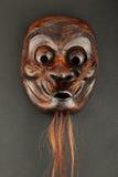 Maschera di protezione scolpita di legno giapponese del teatro sul nero Immagini Stock