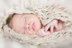 Maschera di un bambino appena nato che dorme su una coperta Fotografia Stock