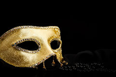 Maschera dorata vicino alle perle sul nero immagini stock libere da diritti
