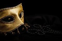 Maschera e perle dorate sul nero fotografia stock