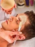 Maschera facciale del fango dell'uomo nel salone della stazione termale Massaggio di fronte immagine stock libera da diritti