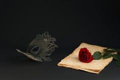 Maschera nera di carnevale e una rosa su un fondo grigio Fotografia Stock