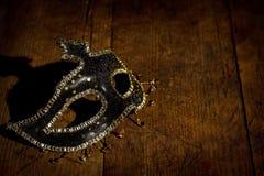 Maschera nera e dorata sulla tavola di legno fotografia stock
